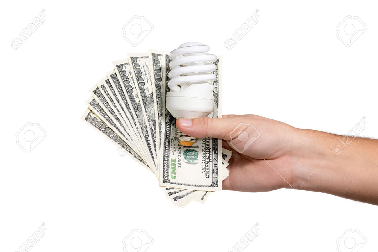 Male hand holding a fan of hundred-dollar bills, and energy-saving light bulb - 49180468