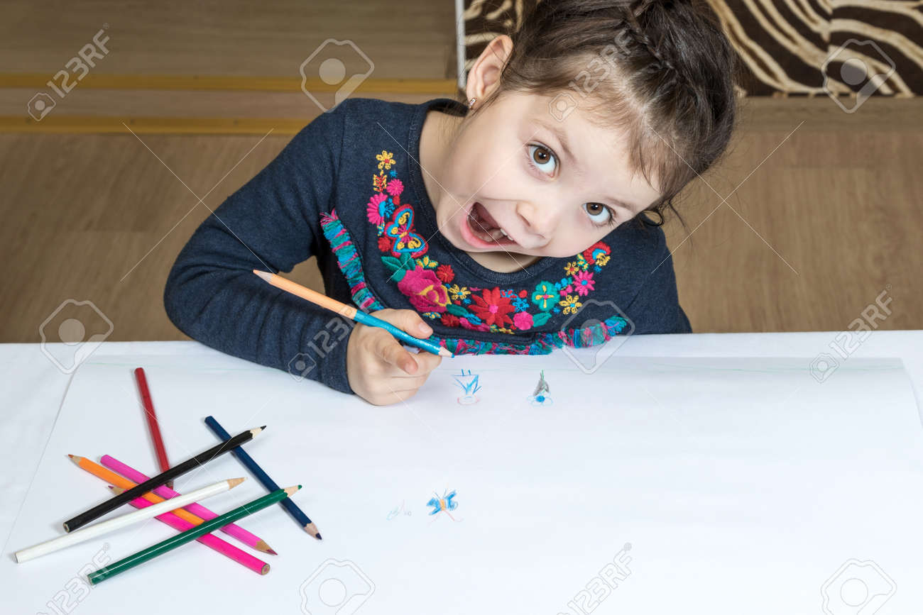 Little girl draws pencil on a large white paper emotional mouth open - 50296250
