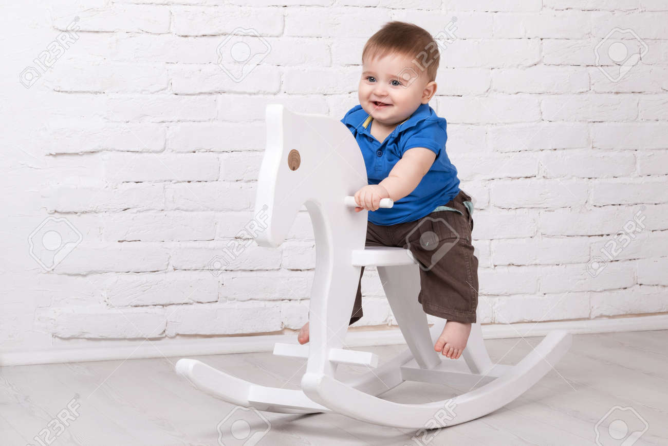 Little smiling baby sitting on a white horse, wooden rocking - 52804015