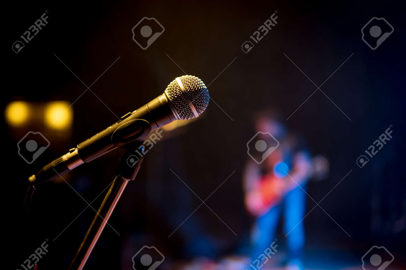 Classic microphone on the stand at a concert in the dark - 89249465