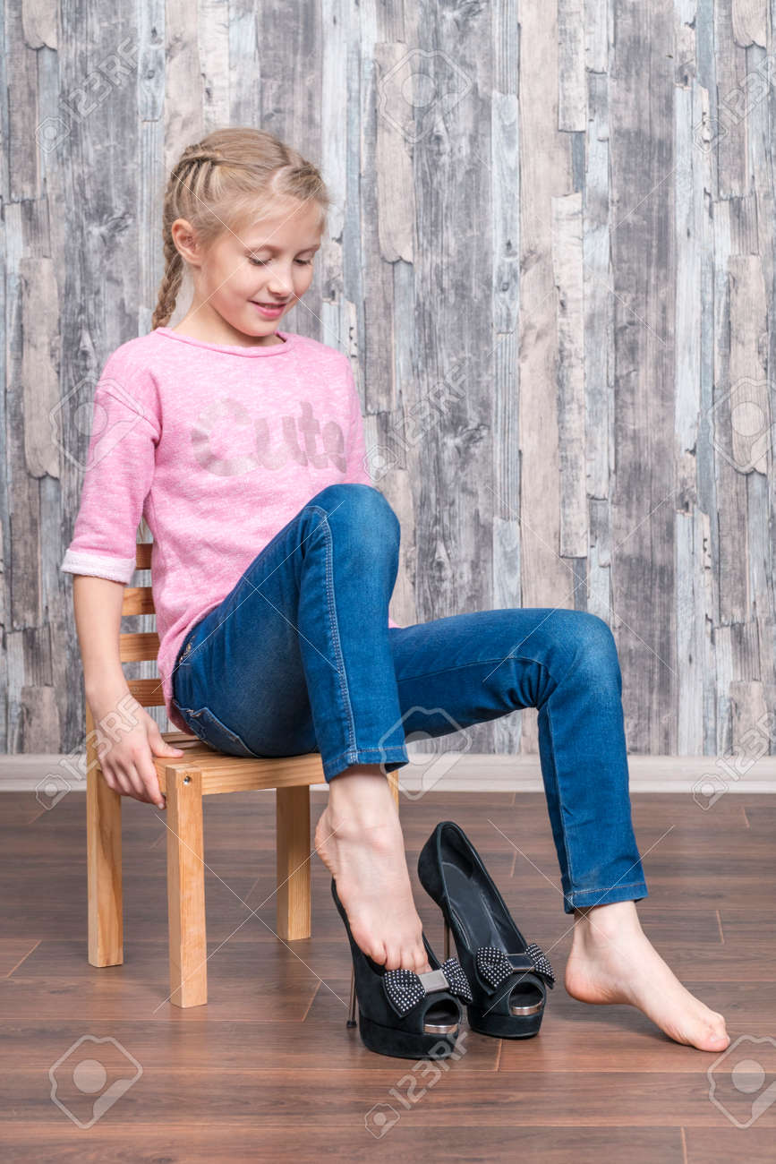 Little Beautiful Girl Sits On A Chair
