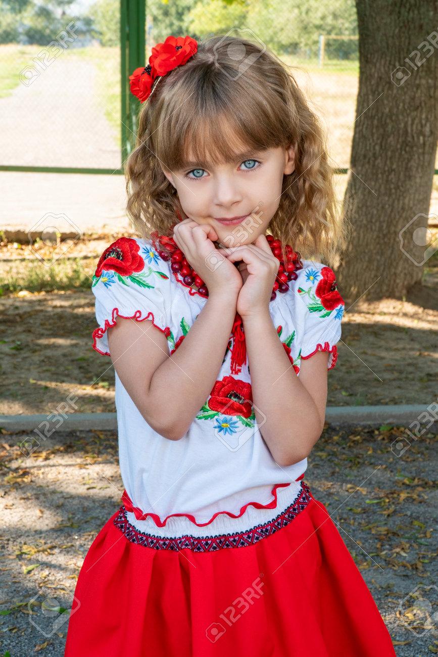 portrait of a beautiful little preschool girl wearing an embroidered shirt - national Ukrainian costume - 166632226