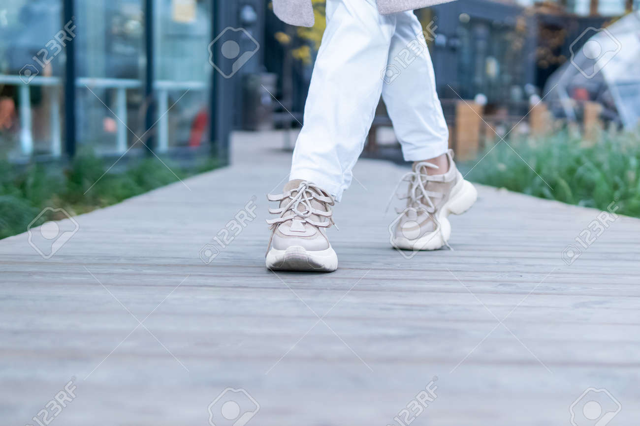 feet in sneakers on the road - 170936557
