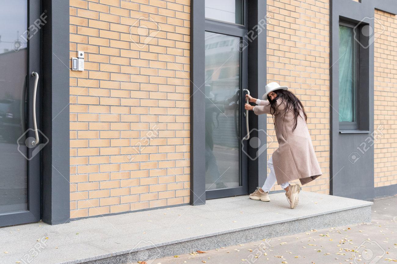 Woman in coat pulls the door - 170935813