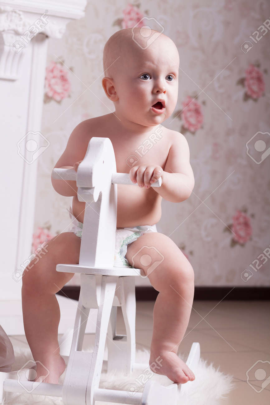 Funny Baby In Diapers Is Sitting On A White Wooden Toy Horse Stock Photo Picture And Royalty Free Image Image 125946830