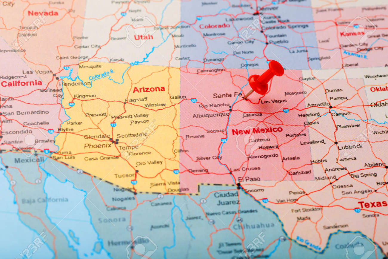 Red clerical needle on a map of USA, New Mexico and the capital..