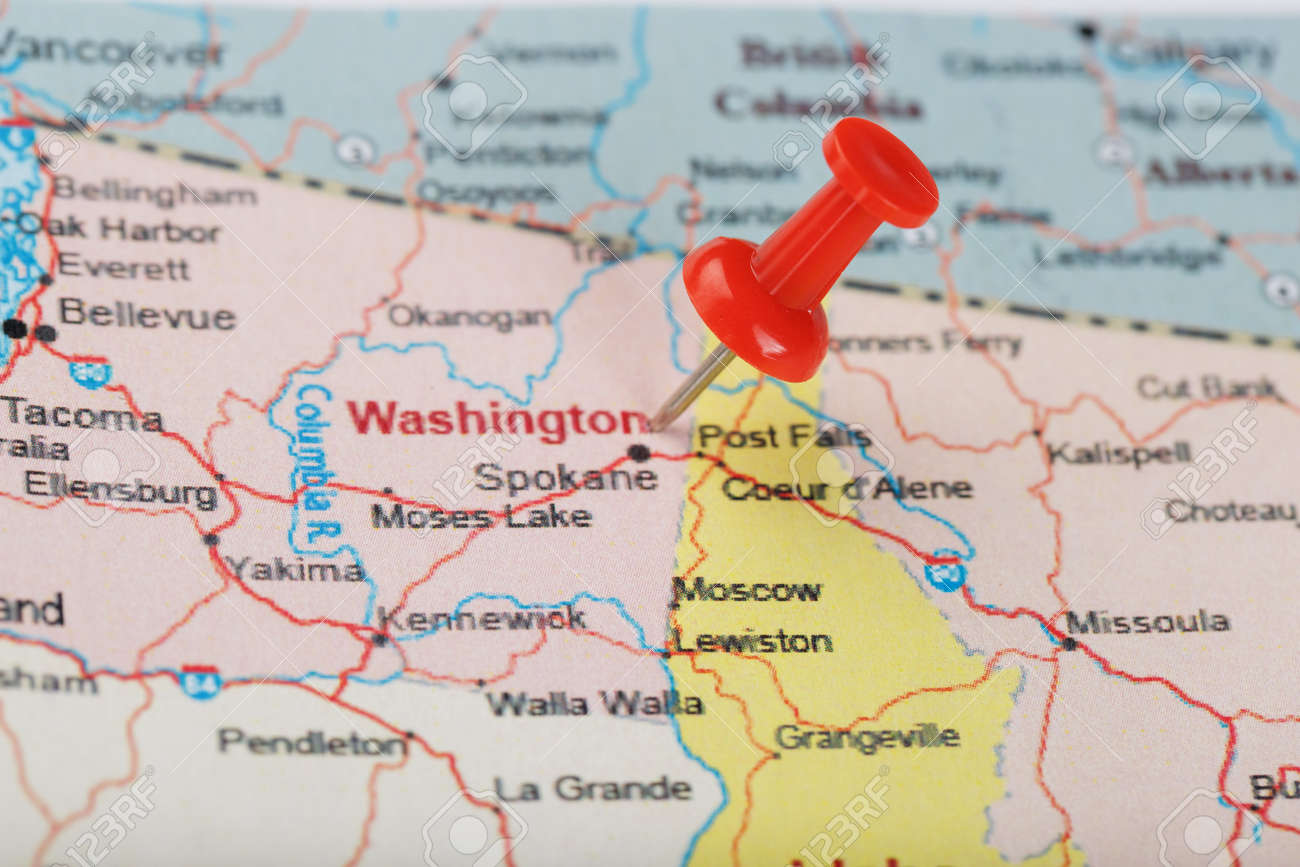 Red clerical needle on a map of USA, Wyoming and the capital..