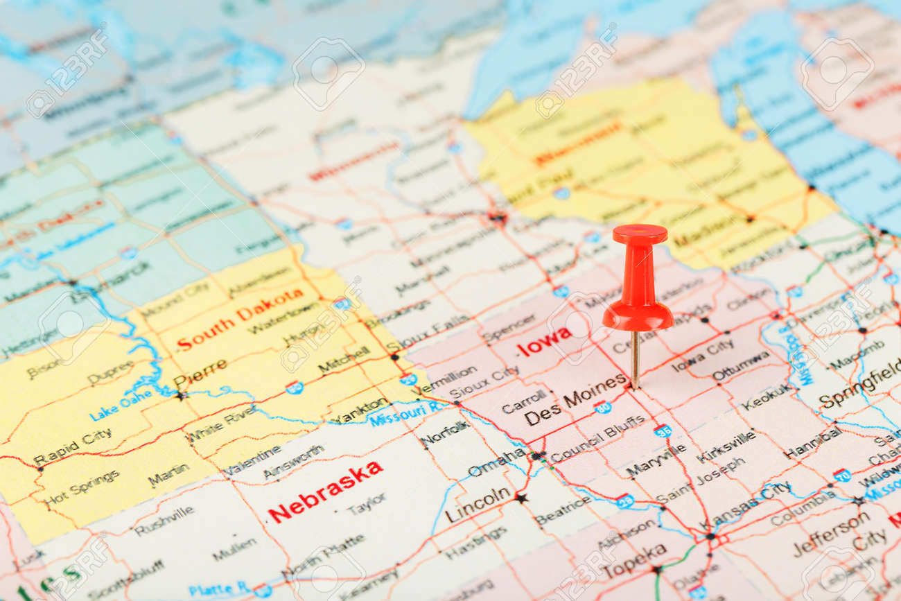 Red clerical needle on a map of USA, Iowa and the capital Des..