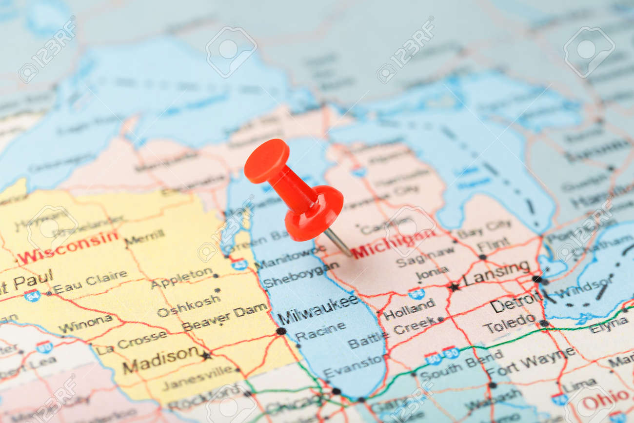 Red clerical needle on a map of USA, Michigan and the capital..
