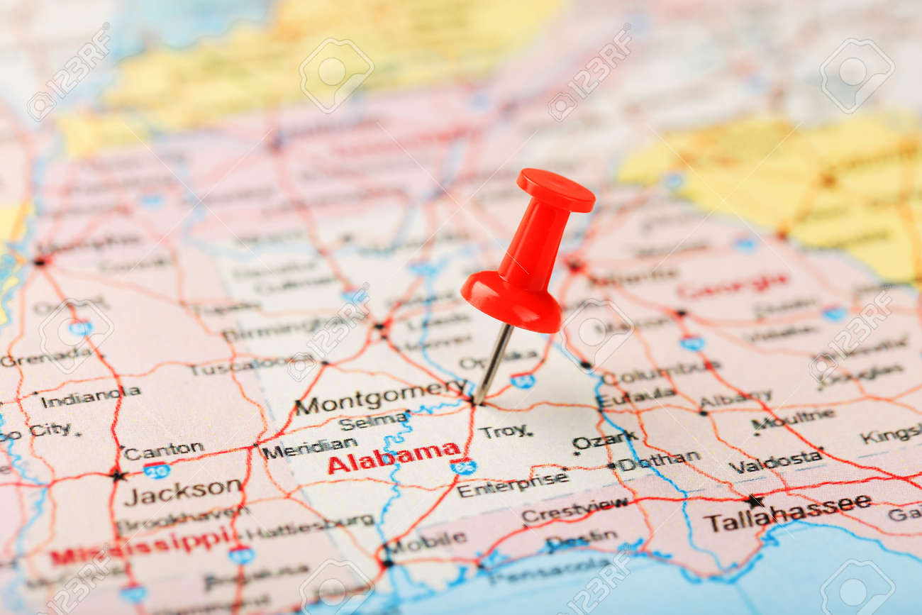 Red clerical needle on a map of USA, South Alabama and the capital..