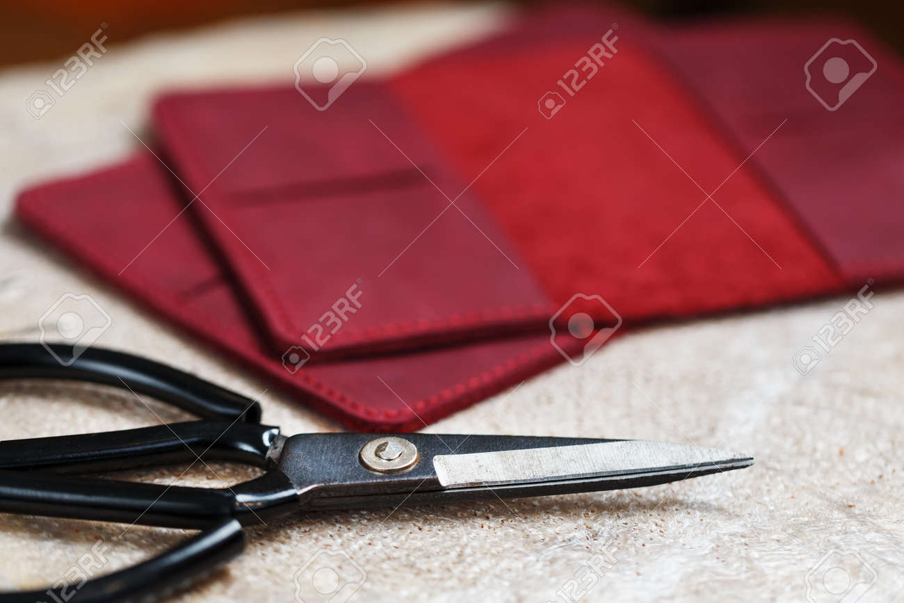 A leather craftsman works with leather. Sews leather goods. Making things handmade. - 142033608