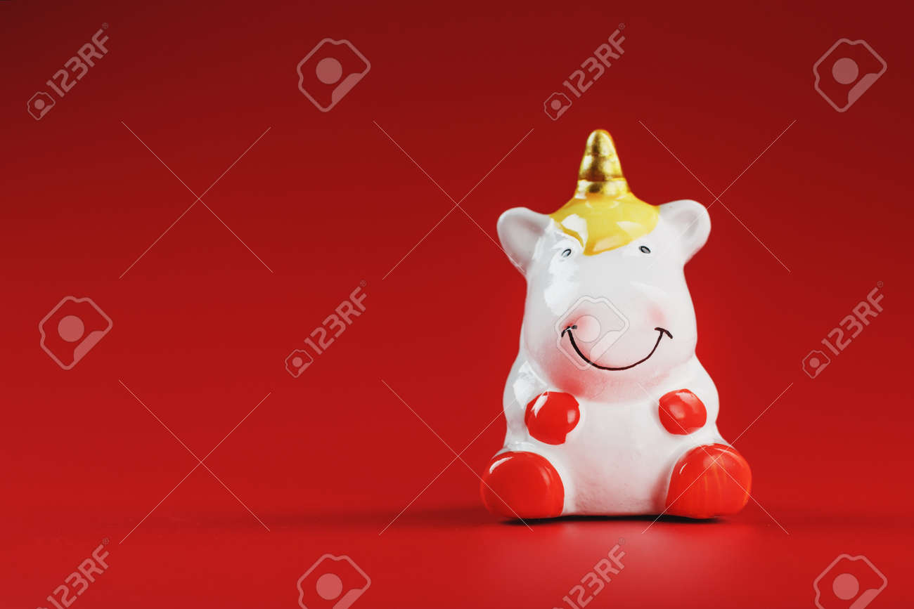 Small figure of a unicorn on a red background. The concept of magic, children's dreams. Free space. - 165524381