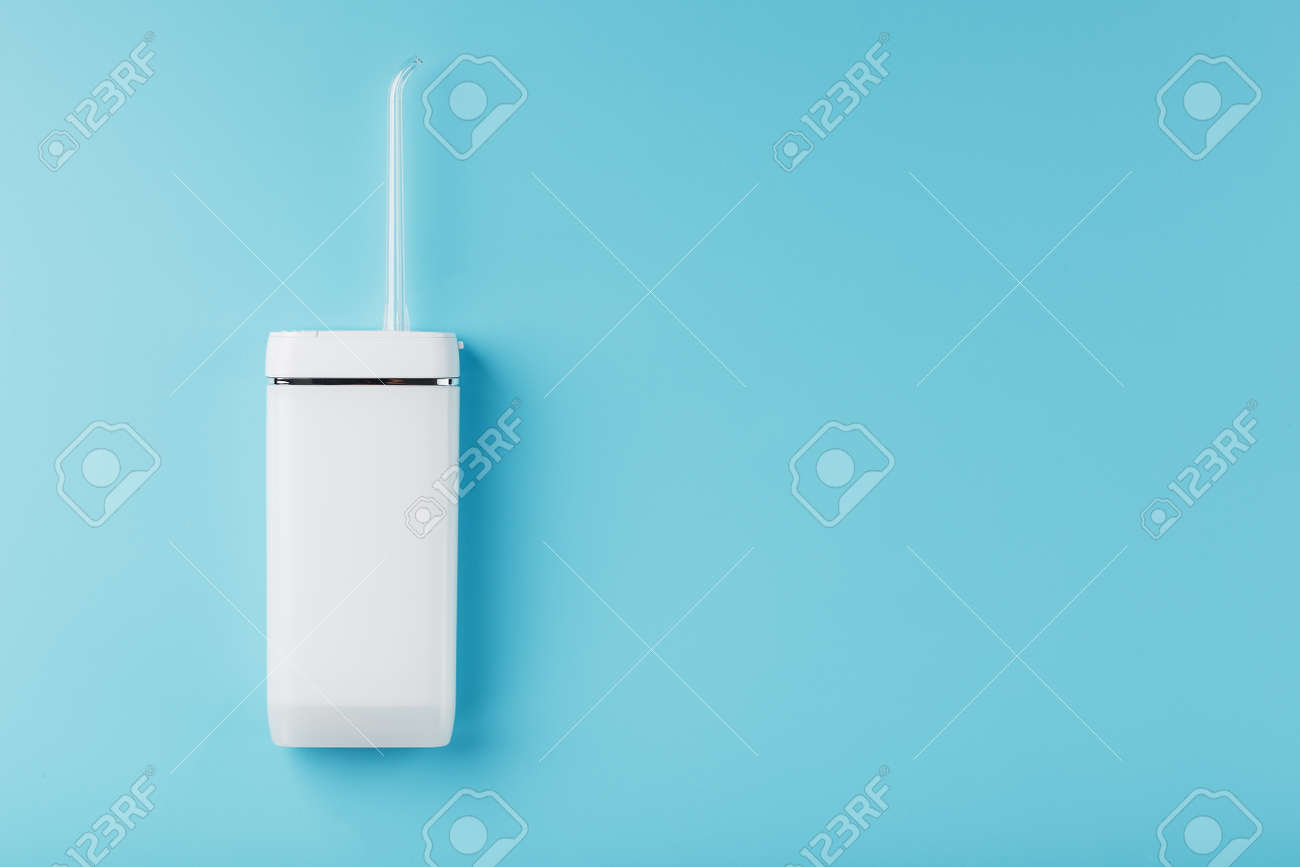 Mobile irrigator for cleaning the oral cavity on a blue background. For brushing your teeth and a snow-white smile. Free space - 169206292
