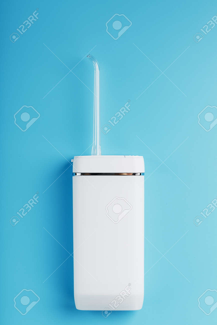 Mobile irrigator for cleaning the oral cavity on a blue background. For brushing your teeth and a snow-white smile. Free space - 169206295