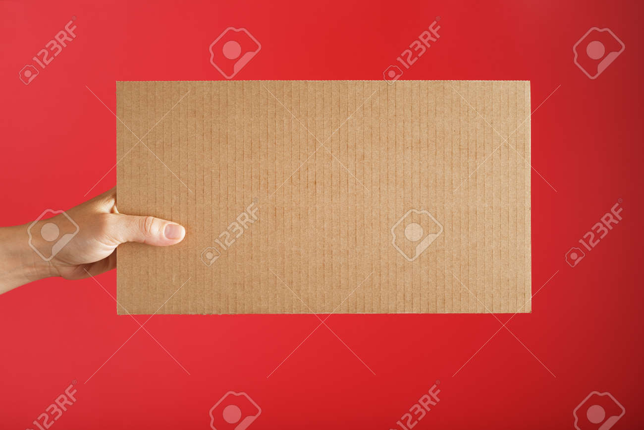 Hand holding a blank sheet of cardboard on a red background. Space for text - 169206344