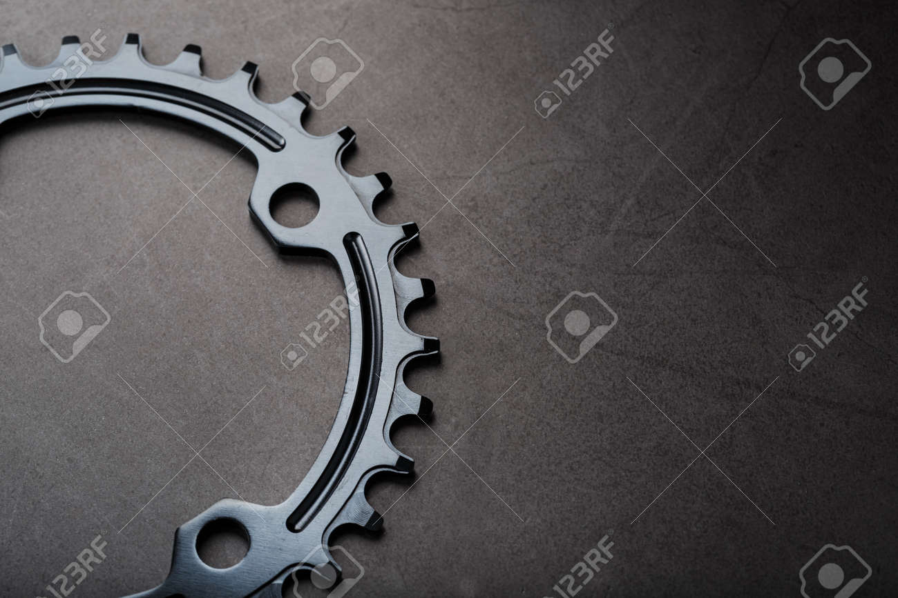 Black Star of the Narrow Wide Bicycle Connecting Rod System. A pattern of teeth of a running bicycle star on a black background. Dark key, top view - 169206388