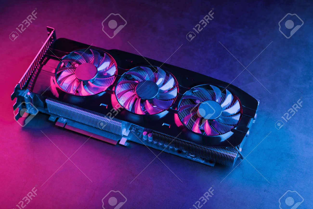 Large and powerful graphics card with three fans with blue pink light. The concept of a cyberpunk video chip for gaming and cryptocurrency mining. Dark key, top view - 169206456