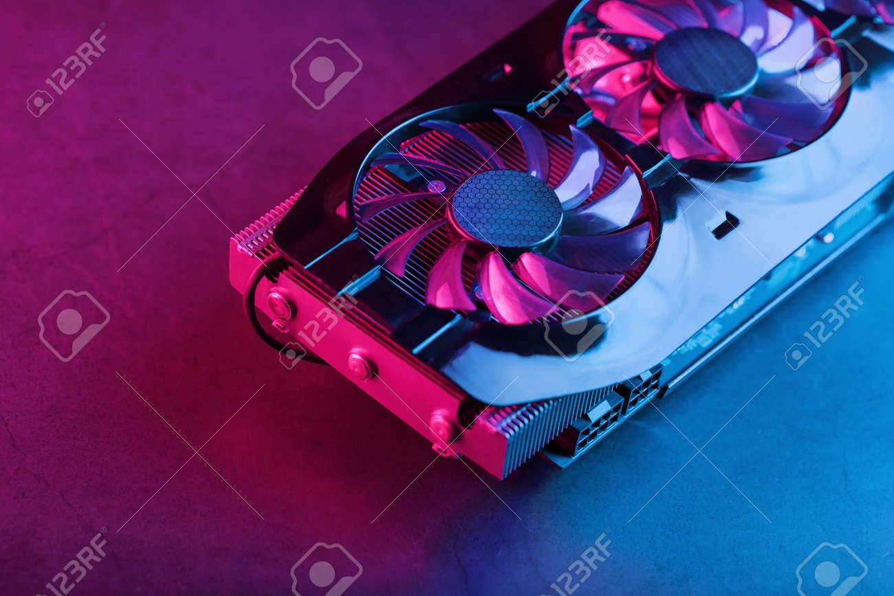 Large and powerful graphics card with three fans with blue pink light. The concept of a cyberpunk video chip for gaming and cryptocurrency mining. Dark key, top view - 169206503