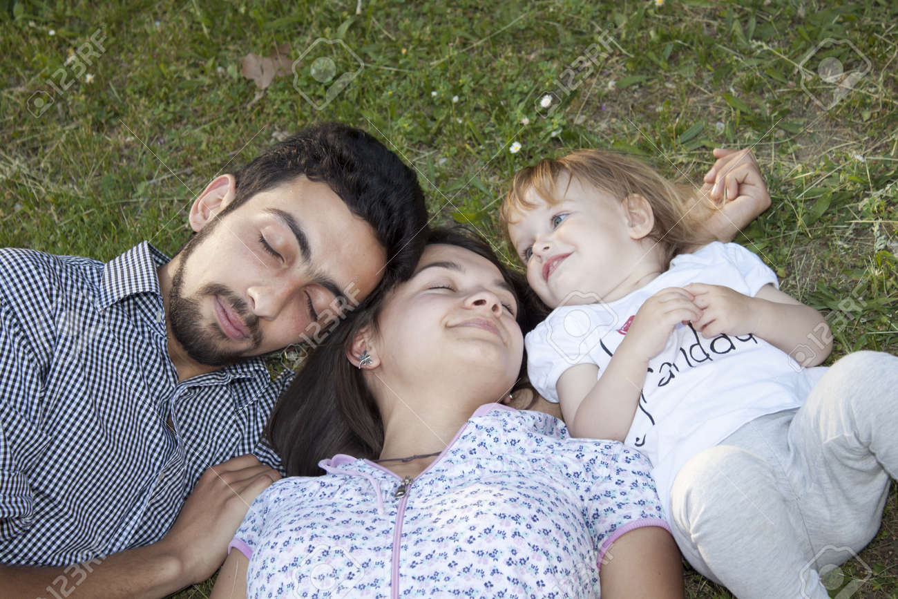 Couple with baby lying on the ground Stock Photo - 13587298