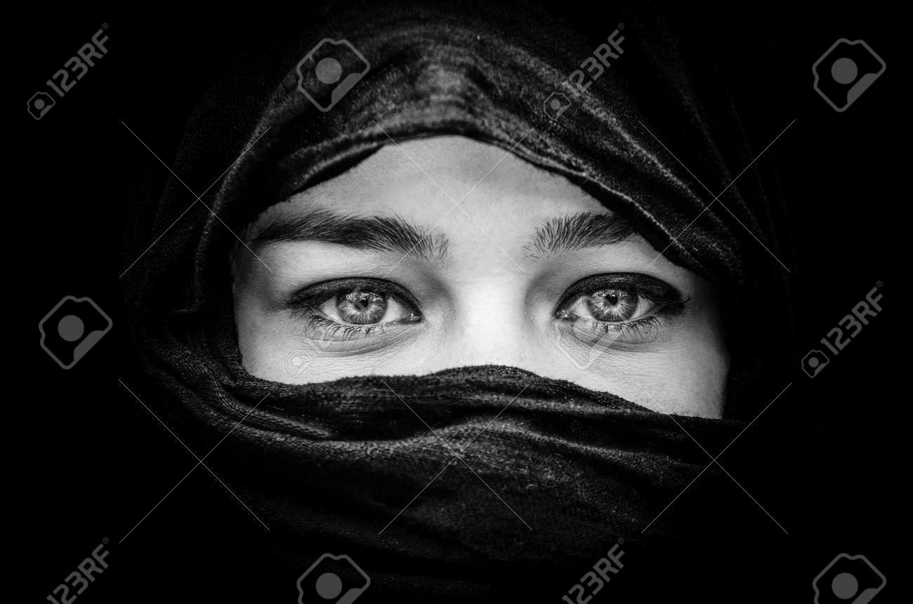 Portrait of beautiful woman with blue eyes wearing black scarf in black and white stock photo