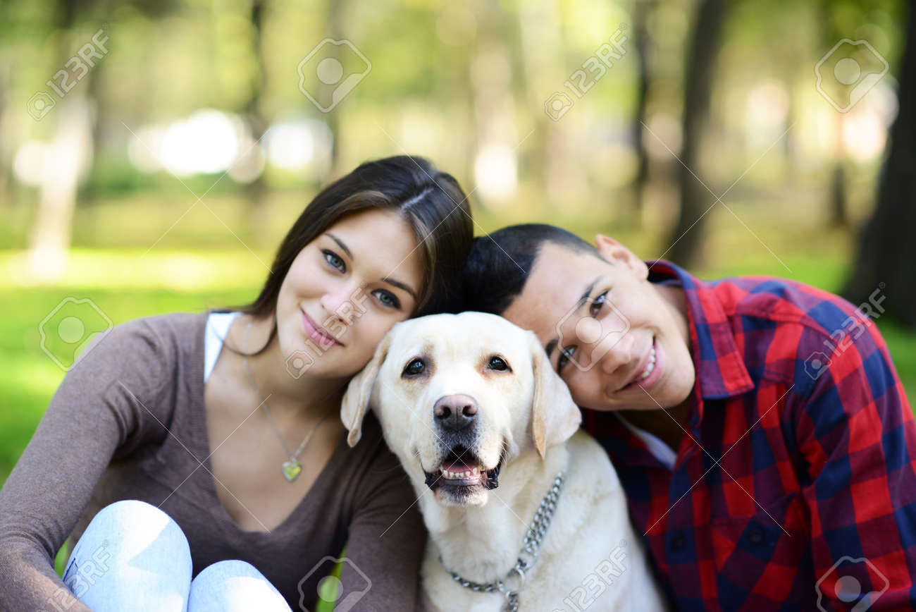 Happy couple with puppy dog at park - 23747311