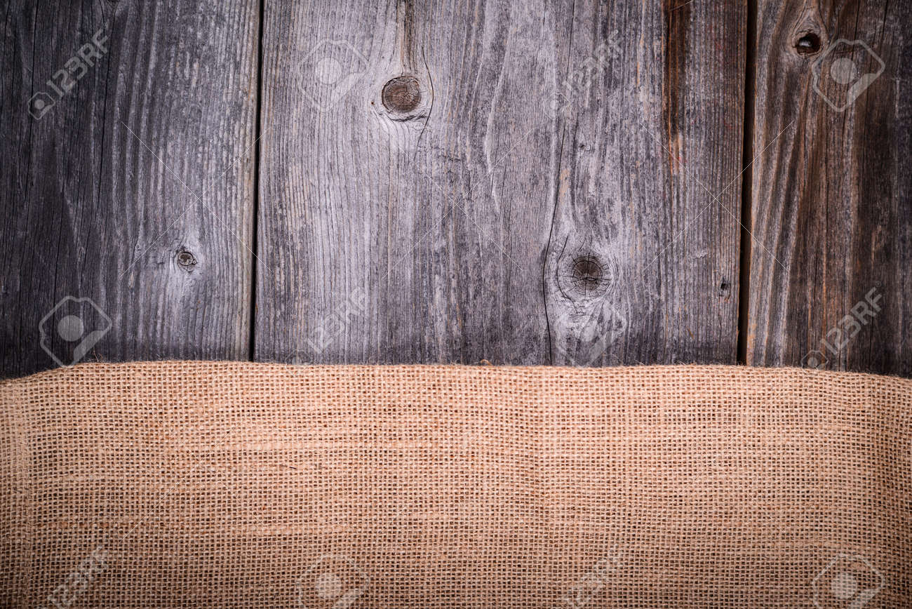 Vintage coffee sack against wooden background - 23747624