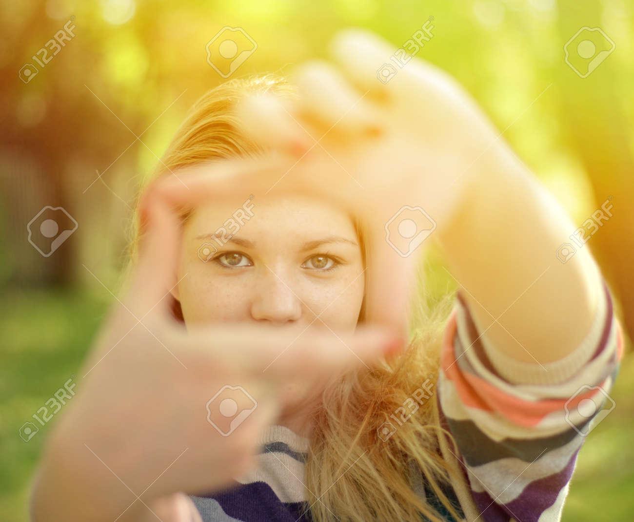 Schönes Mädchen, Die Rahmen Mit Den Händen, Während Im Freien ...