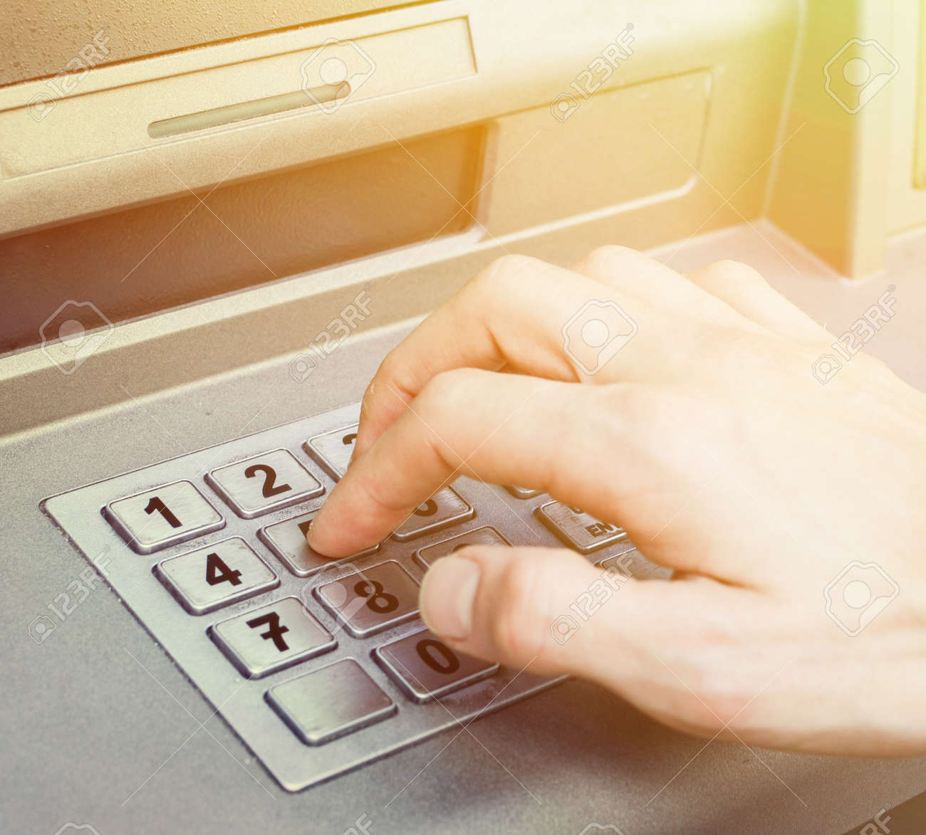 Hand entering PIN numbers on ATM bank machine - 40304854