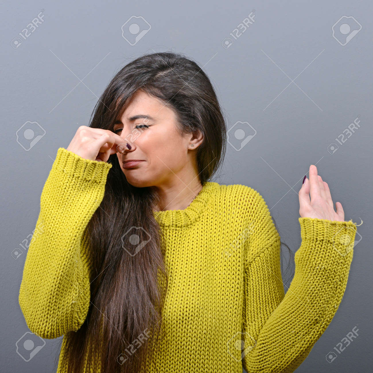 Portrait of woman covering nose with hand showing that something stinks against gray background - 53915052