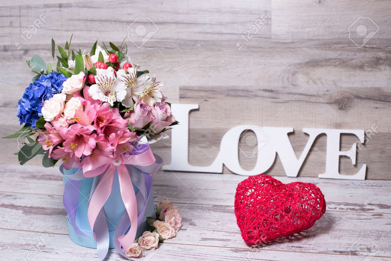 6d4e853ea17 beautiful floral arrangement in a hat box with the inscription LOVE and  action figure heart