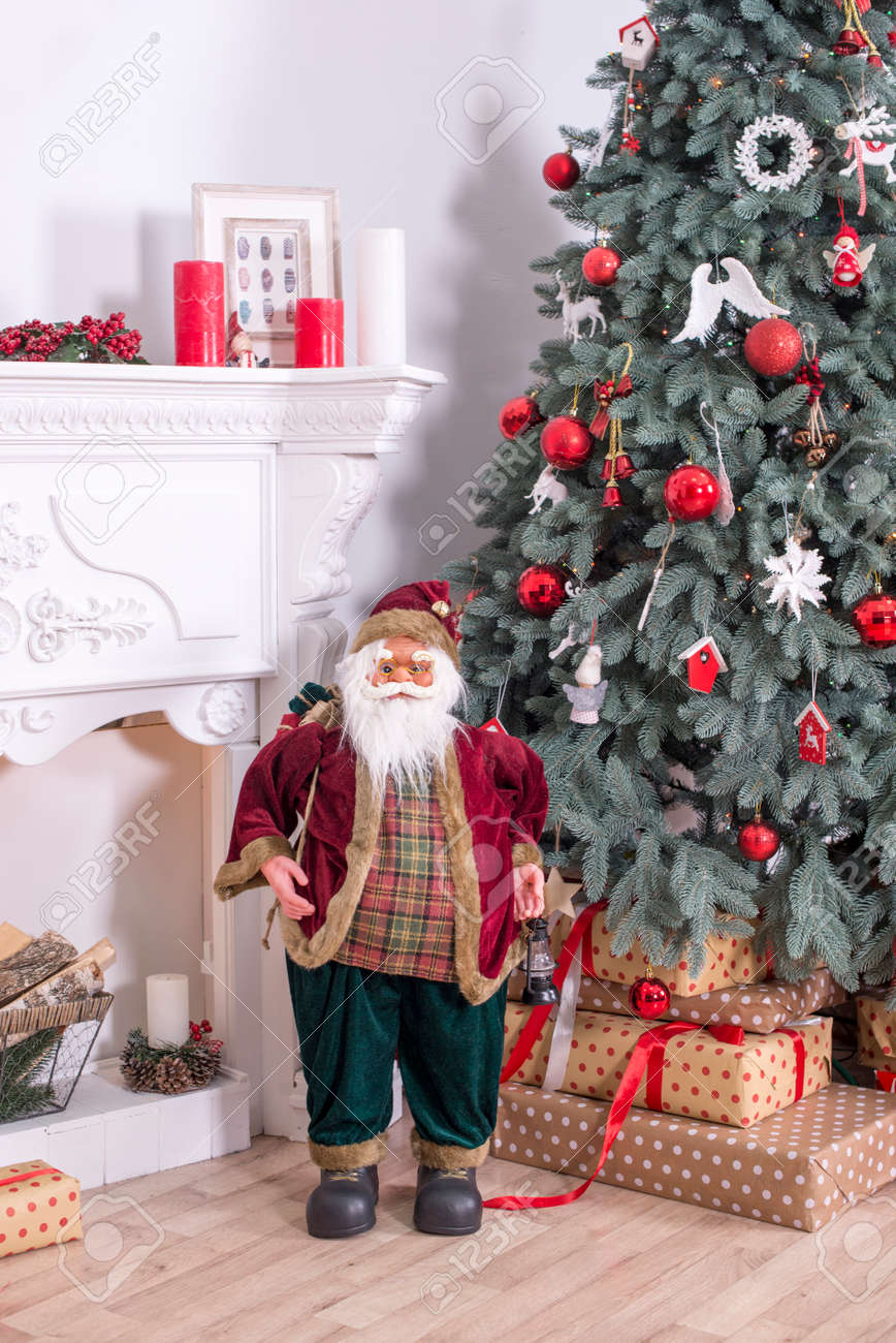Happy Santa Claus Playing With Toys Under The Christmas Tree