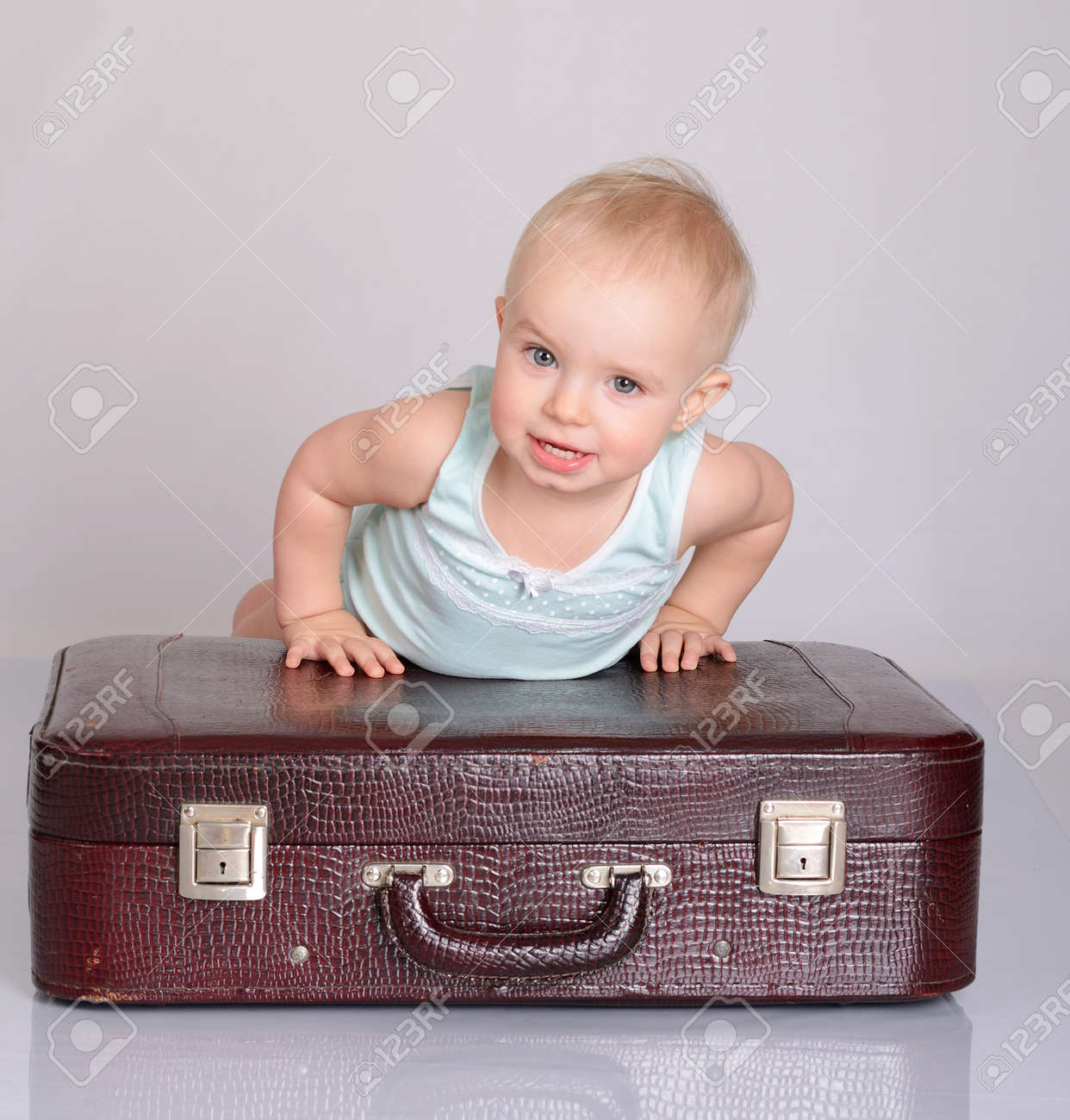 cute baby girl playing with suitcase on grey background Stock Photo - 18124755