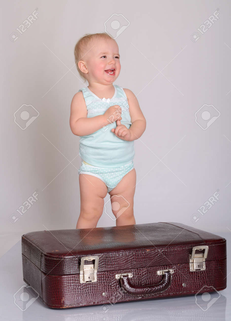 cute baby girl playing with suitcase on grey background Stock Photo - 18124670