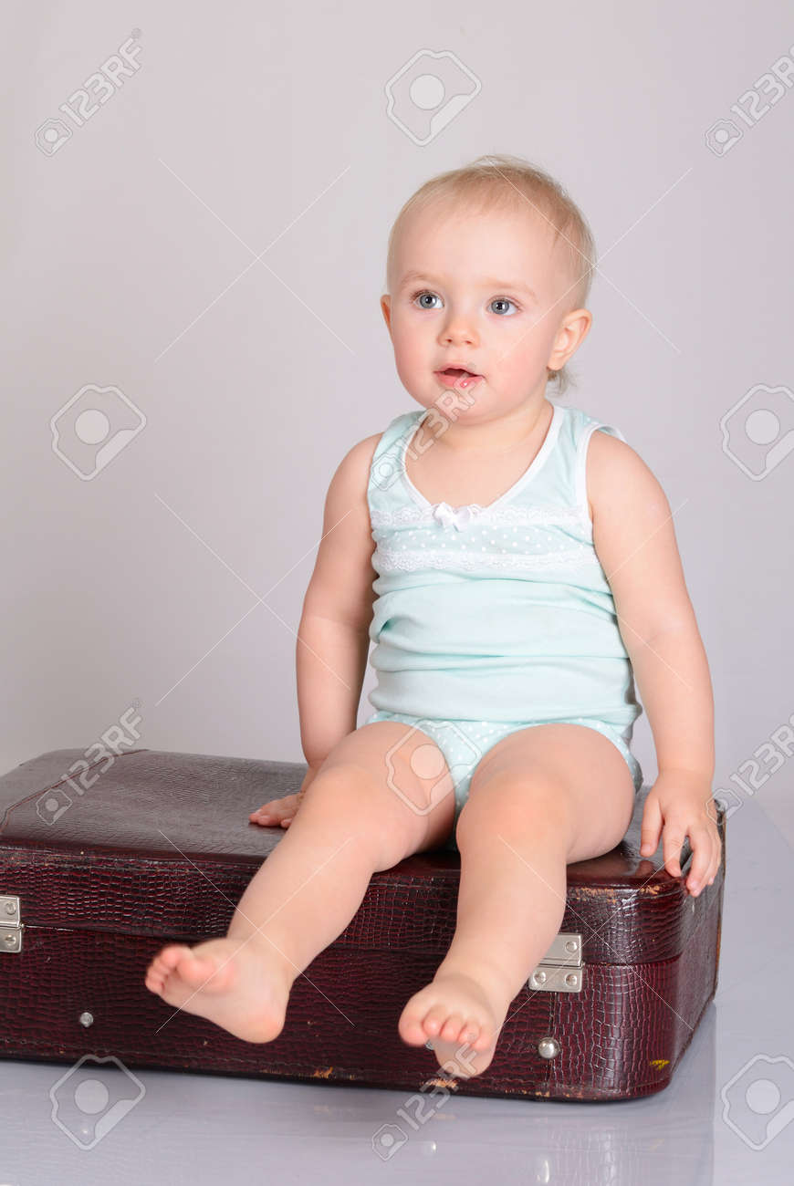 cute baby girl playing with suitcase on grey background Stock Photo - 18124758