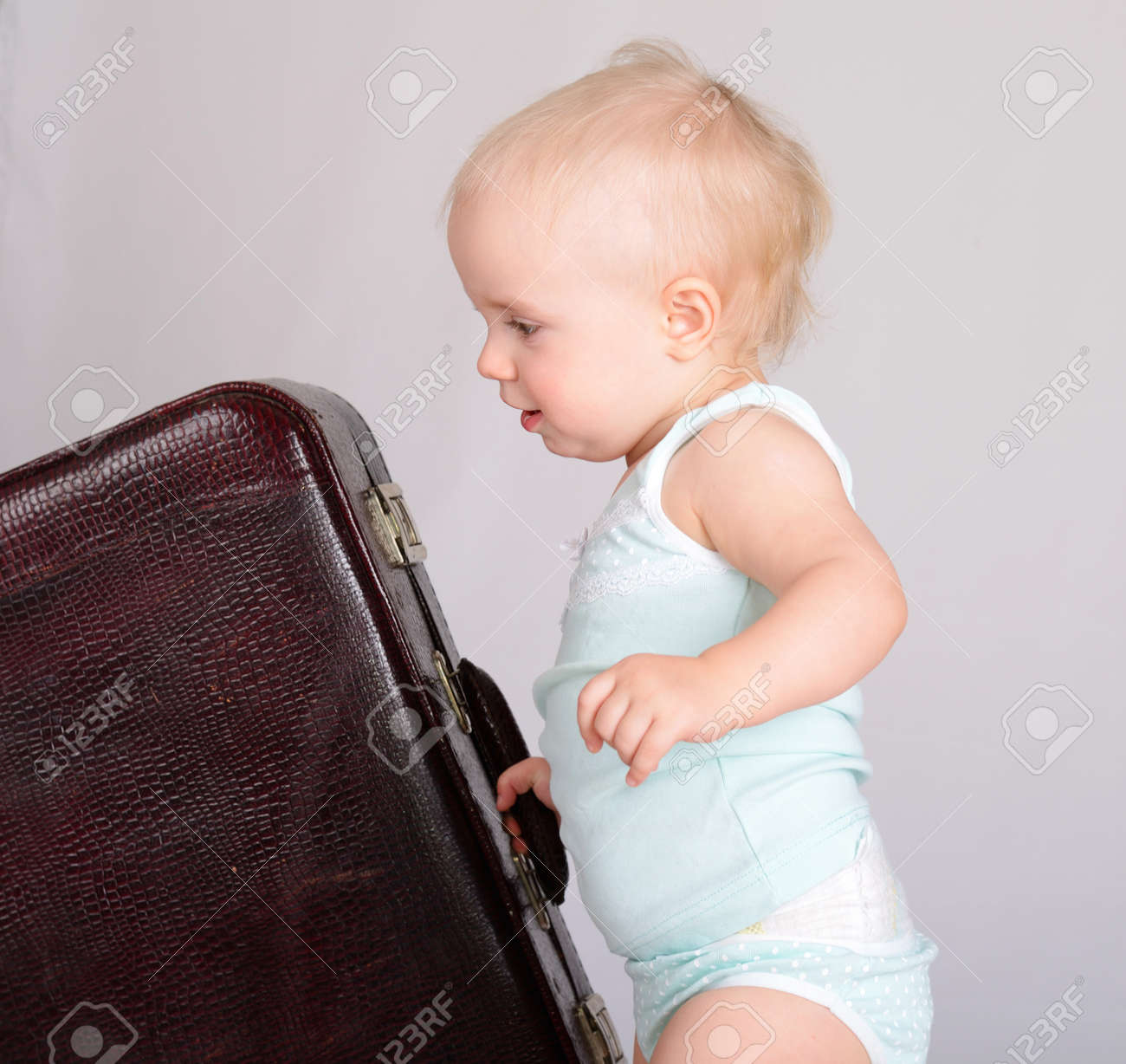 cute baby girl playing with suitcase on grey background Stock Photo - 18124750