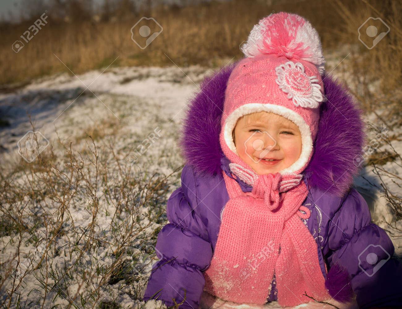 Portrait of happy little girl in snowy landscape - 24370450