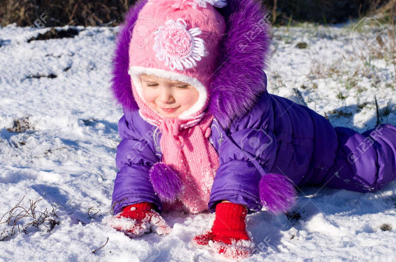 Portrait of happy little girl in snowy landscape - 24370452