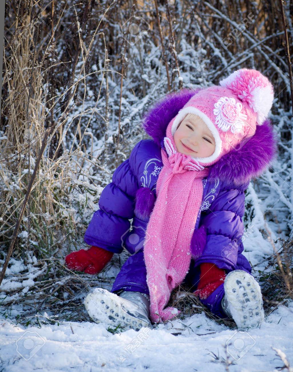 Portrait of happy little girl in snowy landscape - 24370456