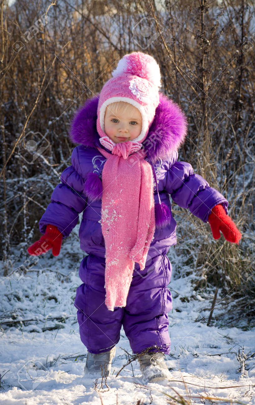 Portrait of happy little girl in snowy landscape - 24370584