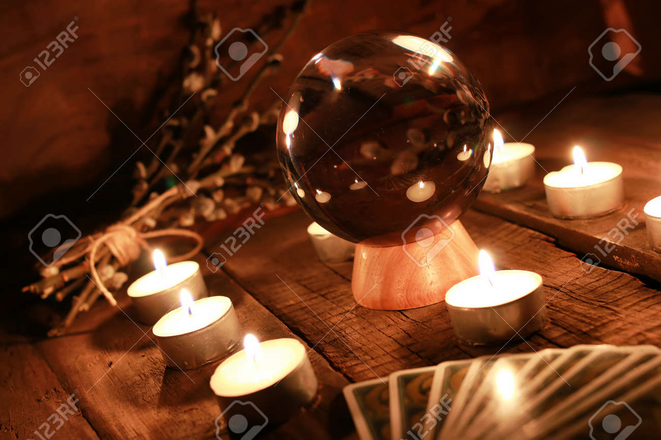 crystal ball for predicting the fate and supernatural action on the table from the old mahogany with candles and cards - 65080587
