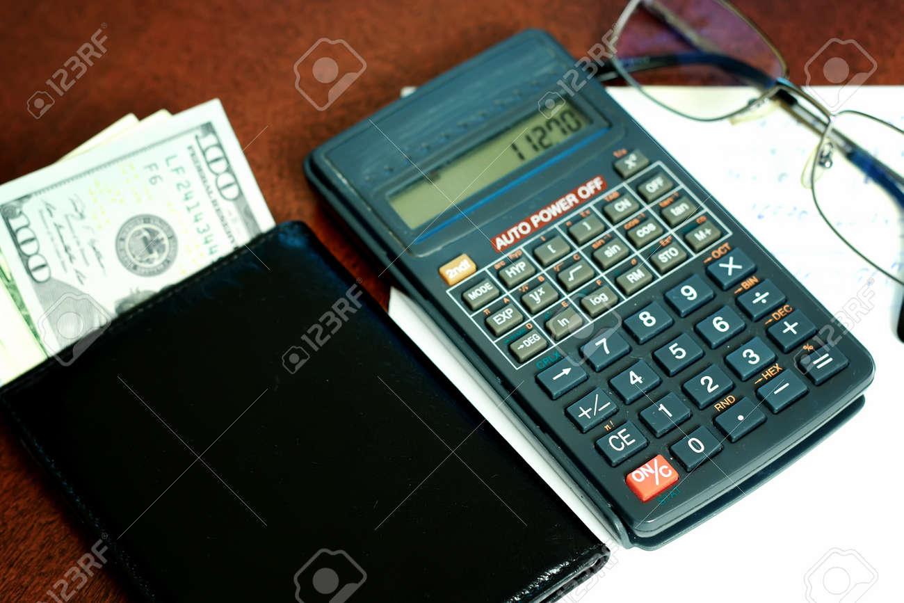 Calculadora gris en una mesa de madera y una pila de dinero para el cálculo  de ae71742c2822c