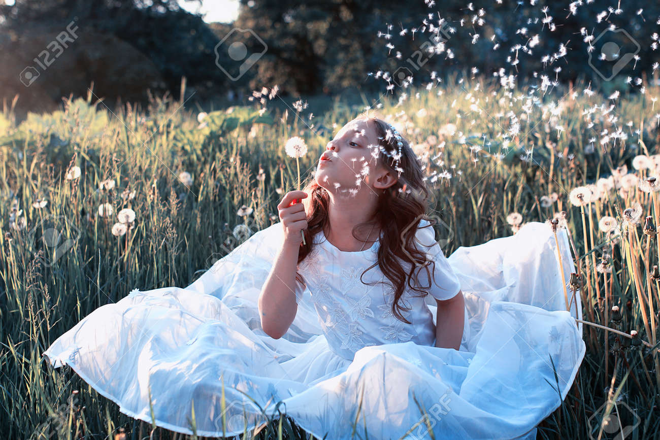 Teen girl blowing seeds from a flower dandelion in spring park Stock Photo - 76093233
