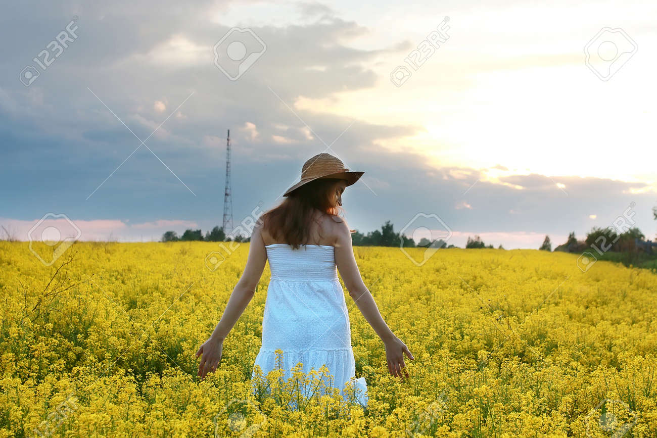 Girl In Straw Hat In A Field Of Yellow Flowers Blossoming Stock