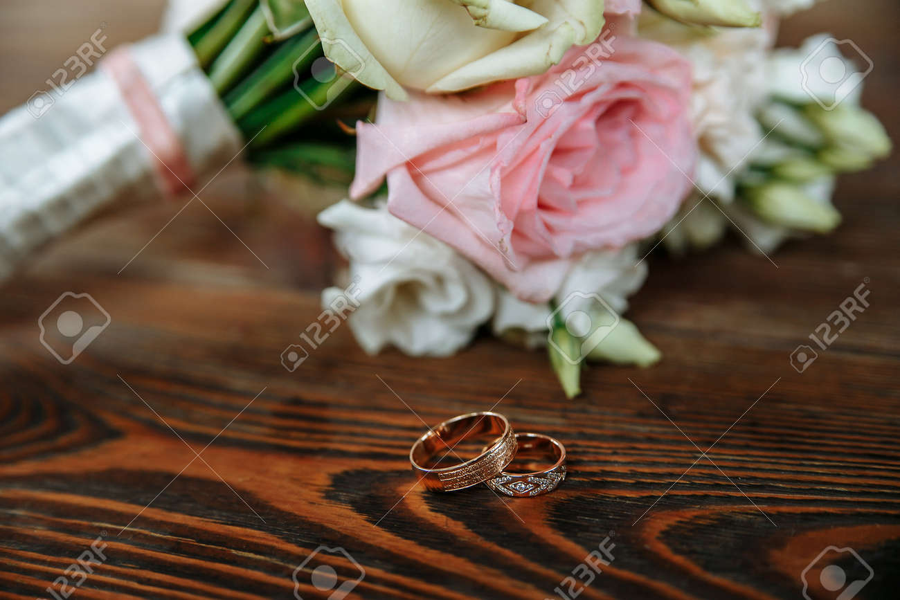 Wedding Bouquet Of Cream And Pink Roses Lies On A Wooden Surface