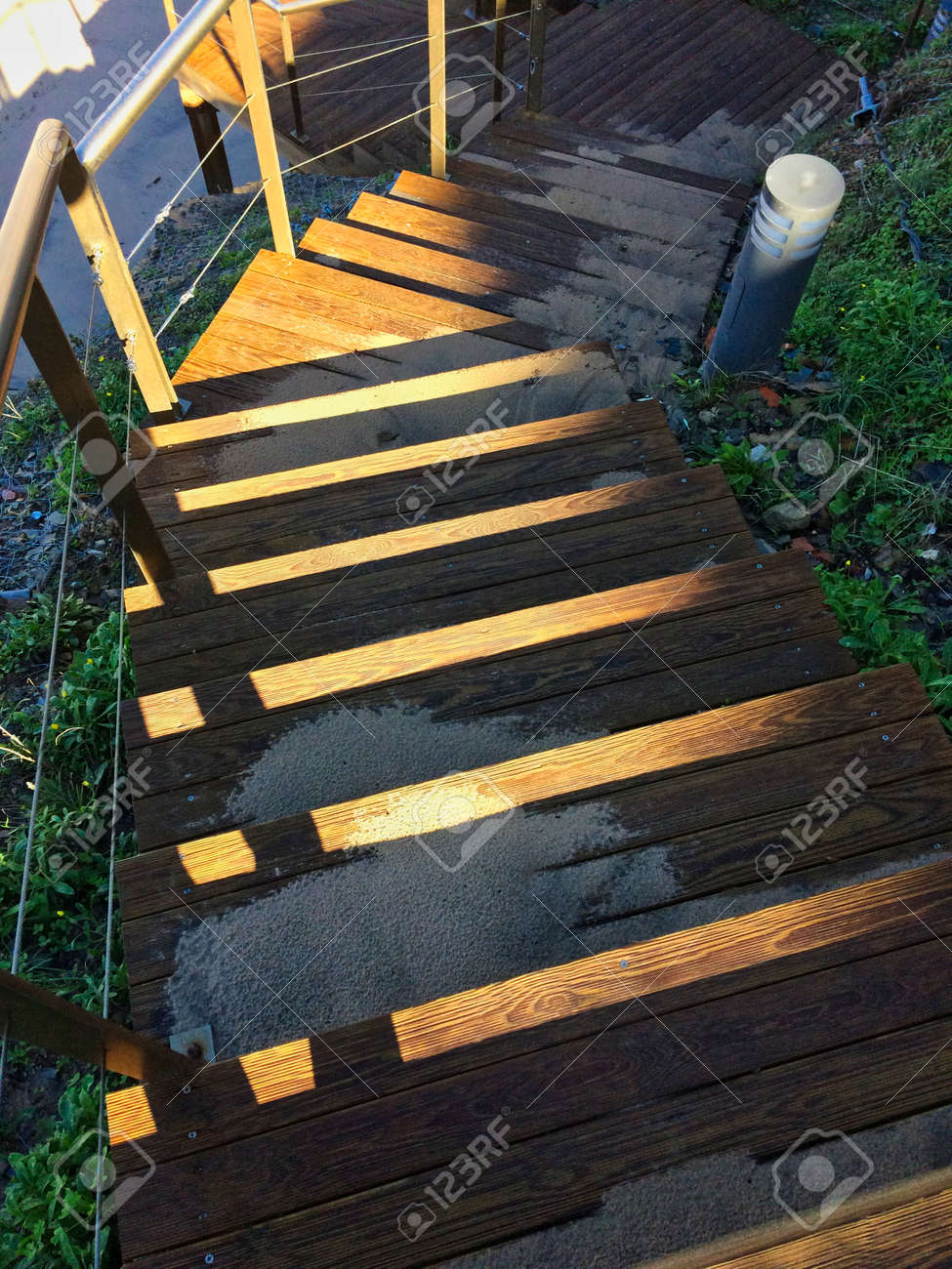 steep wooden staircase leading down, sand scattered on the steps,