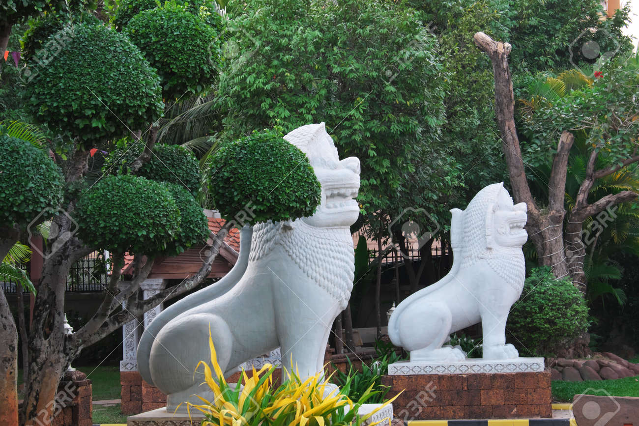 Two White Stone Sculptures Of Lions Near Beautifully Trimmed