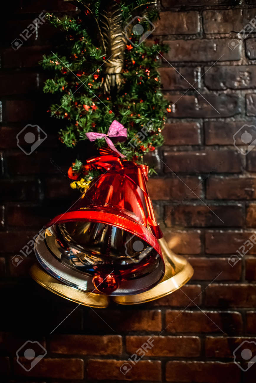 red christmas bell hanging on brick wall as decorative christmas decoration stock photo 71647634