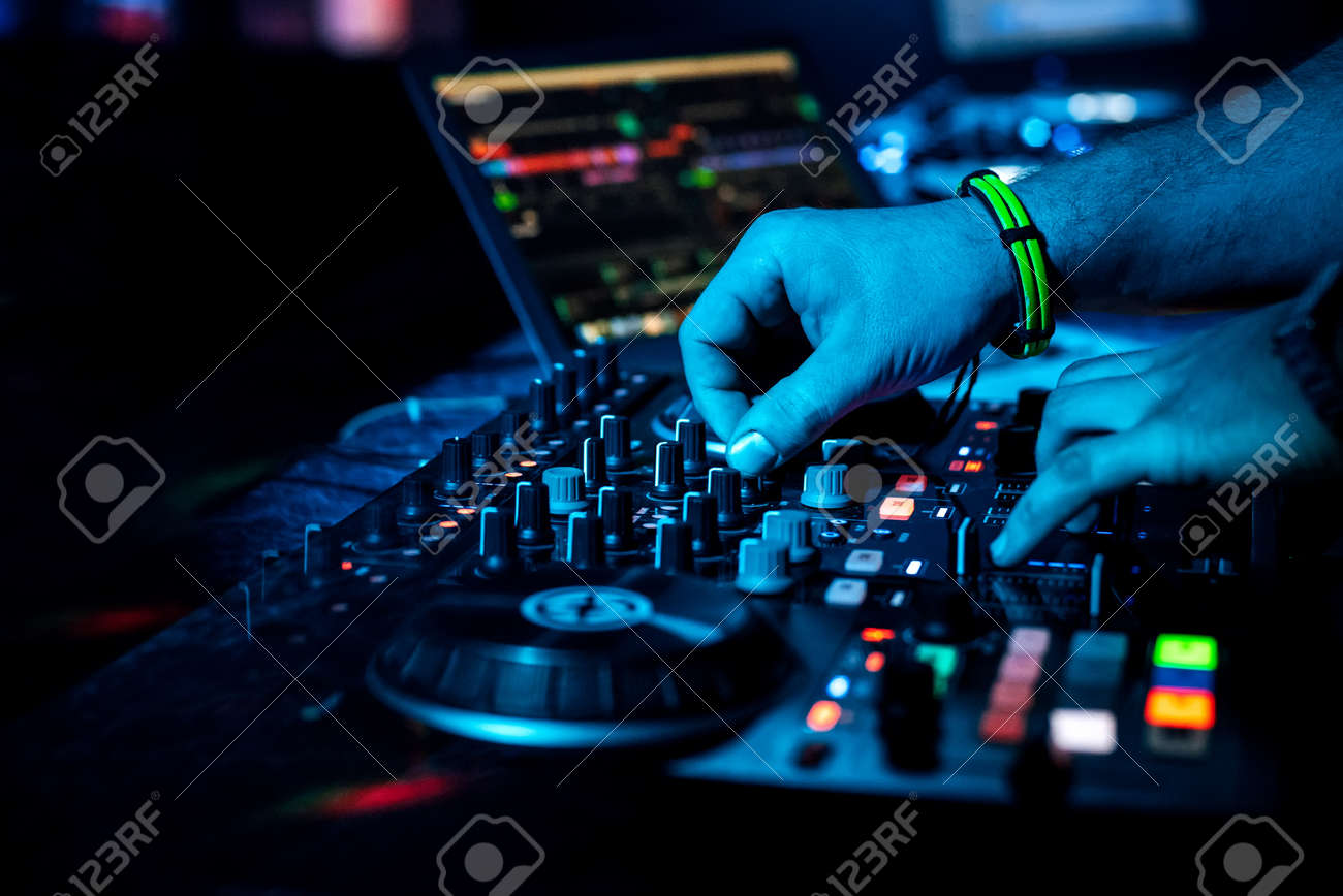 DJ hand mixes electronic music on a professional mixer in a nightclub at a concert - 142121083
