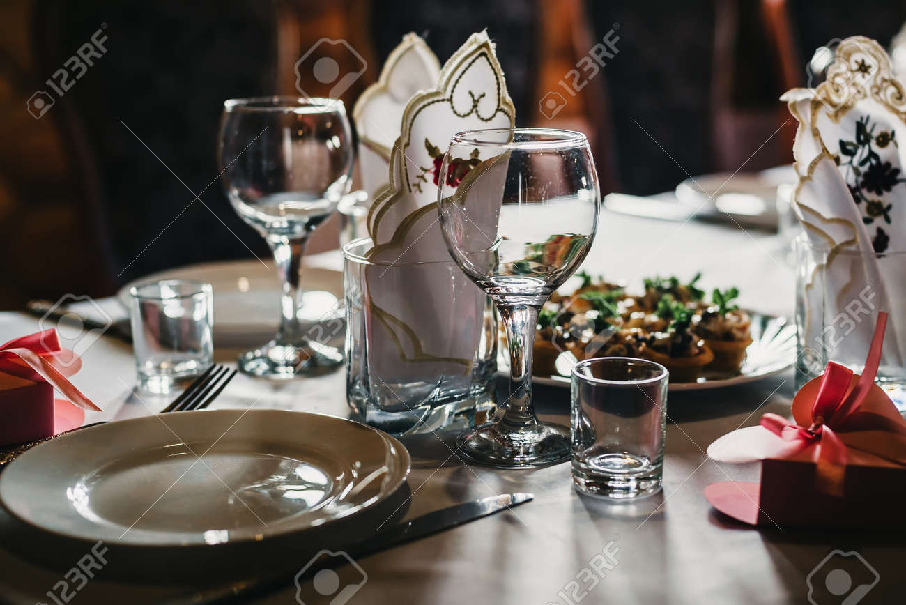 set of empty glasses and plates with Cutlery on a white tablecloth on the table in the restaurant - 147257148