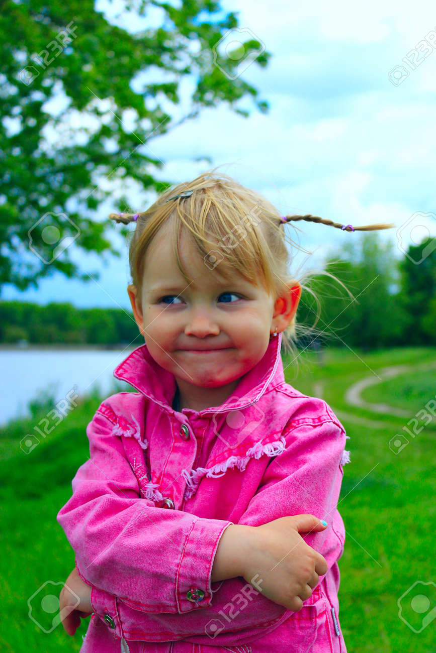 pretty fashionable smiling baby girl with nice plaits near the
